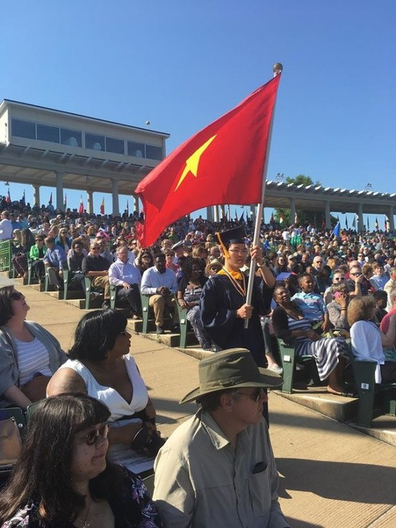 Le Quang Liem carries the Vietnamese flag at Webster University's graduation ceremony in the US (Photo: dantri.com.vn)