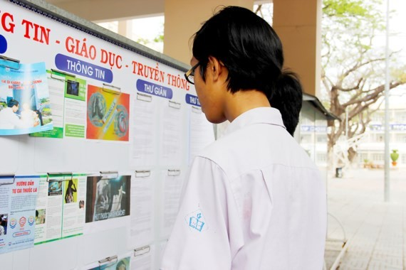 Students read poster of tobacco harm (Photo: SGGP)