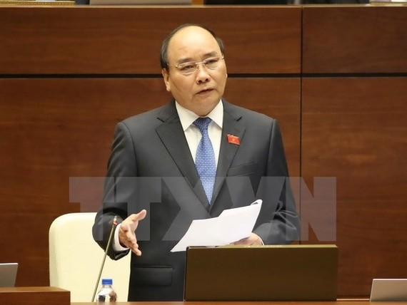Prime Minister Nguyen Xuan Phuc answers questions at the second working session of the parliament (Photo: VNA)