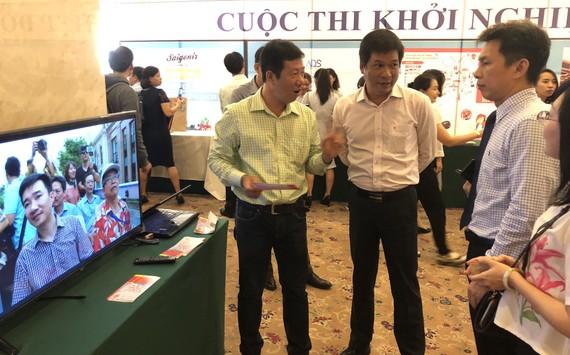 Ông Nguyễn Việt Dũng, Giám đốc Sở KHCN TPHCM (trái) tìm hiểu sản phẩm du lịch của các nhóm khởi nghiệp