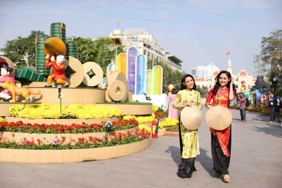Hoa hậu sắc đẹp Việt toàn cầu Bùi Như Ý (phải) và người mẫu Trần Dương dạo bước trên Đường hoa Nguyễn Huệ