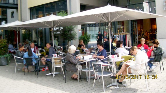 Người dân ngồi sưởi nắng uống cà phê trong một tiệm cà phê ngoài trời tại Đức