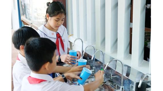 Các em học sinh Trường Tiểu học Hưng Mỹ 2, huyện Mỏ Cày, tỉnh Bến Tre uống nguồn nước sạch.