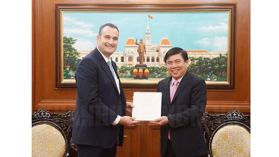 Chủ tịch UBND TPHCM Nguyễn Thành Phong tặng quà lưu niệm cho tân Tổng lãnh sự Canada Kyle Nunas. Ảnh: hcmcpv