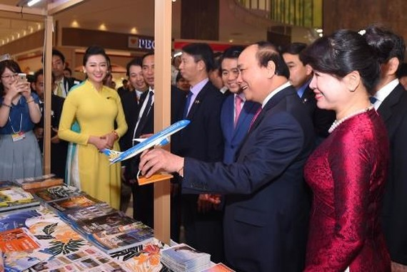 Prime Minister Nguyen Xuan Phuc visits Vietnam Airlines' booth at the event (Photo: VNA)