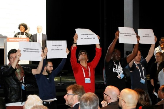 People hold placards during the opening of the 9th International AIDS Society conference on HIV Science on July 23, 2017, in Paris. — AFP/VNA