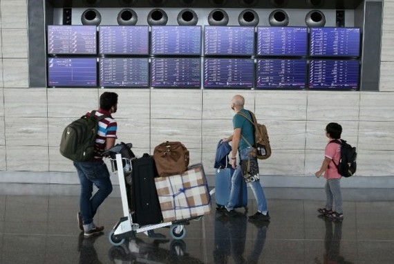 Passengers check the departures board at the Hamad International Airport in Doha on July 20, 2017. — AFP/VNA