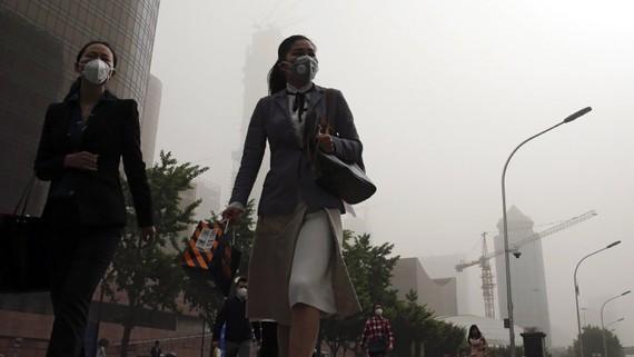 Nhân viên văn phòng ở thủ đô Bắc Kinh phải mang mặt nạ bảo vệ đi làm (tháng 5-2017). Ảnh: AP