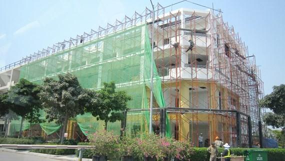 Công trình khi thi công xây dựng phải che chắn để bụi không gây ô nhiễm môi trường Ảnh: HUY ANH