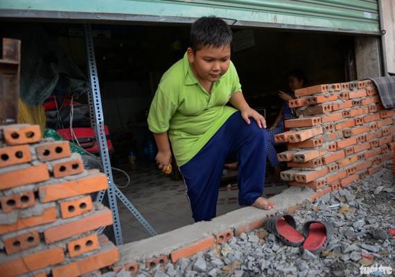Trẻ em cũng phải khom ra vào căn nhà mặt tiền đường Kinh Dương Vương khi mặt đường được nâng lên cả mét khiến các căn nhà ven đường bị che bít lối vào
