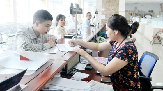 Nhân viên Cục Thuế TPHCM hướng dẫn người nộp thuế làm tờ khai.
