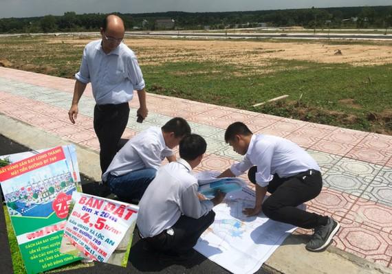 Nhân viên môi giới trải sơ đồ quy hoạch sử dụng đất quanh khu sân bay Long Thành, giới thiệu cho khách hàng khu đất bán trên đường ĐT 769, huyện Long Thành, tỉnh Đồng Nai. Ảnh nhỏ: những tấm biển rao bán đất gần sân bay Long Thành - Ảnh: QUANG ĐỊNH