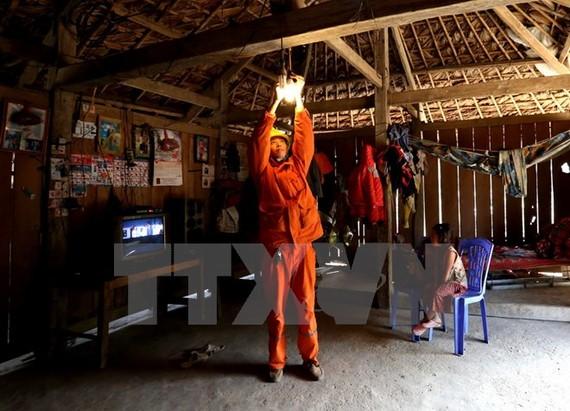 Công nhân Công ty Điện lực Thái Nguyên lắp đèn tiết kiệm điện và hướng dẫn người dân sử dụng điện an toàn. (Ảnh: Ngọc Hà/TTXVN)