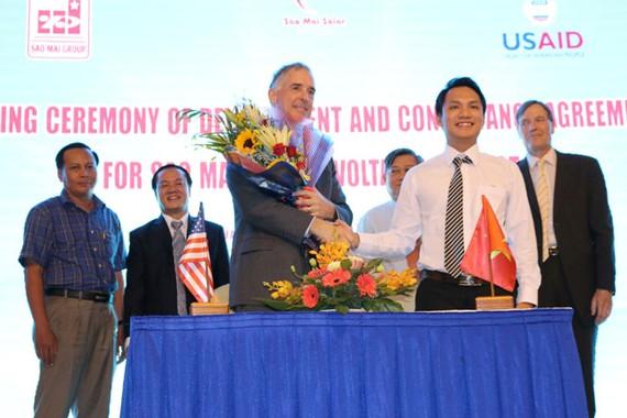 Ông Lê Tuấn Anh, Tổng GĐ Công ty Sao Mai Solar và ông John Bruce Wells, GĐ Dự án V-LEEP thực hiện nghi thức Ký kết phát triển và tư vấn tài chính dự án NLMT 210MW.