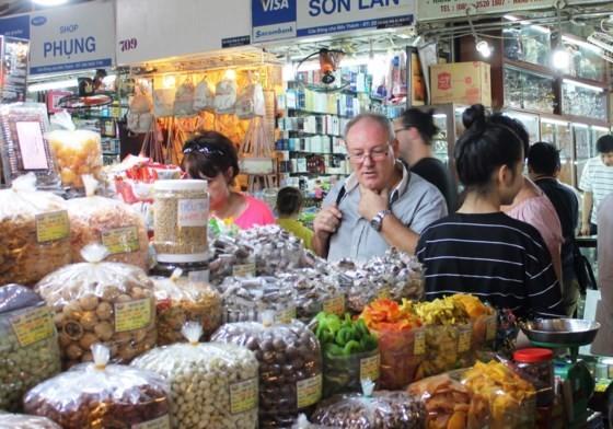 Hơn 90% hàng bày bán tại chợ Bến Thành có xuất xứ trong nước. Trong ảnh: Du khách quốc tế tham quan, tìm hiểu về các mặt hàng thực phẩm bán tại chợ Bến Thành trưa 26-10