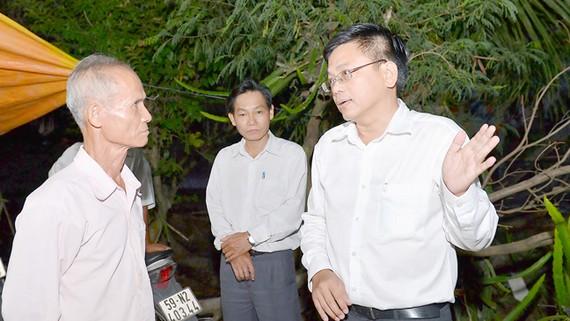 Phó Chủ tịch UBND huyện Bình Chánh Nguyễn Văn Tài (bìa phải) trực tiếp đến nhà ông Võ Văn Kim vào buổi tối để vận động việc giải phóng mặt bằng xây dựng đường cao tốc Bến Lức - Long Thành          Ảnh: VIỆT DŨNG