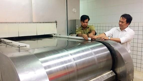 Anh Nguyễn Thanh Hiền (phải) cùng đồng nghiệp bên băng chuyền  cấp đông IQF do anh cải tạo