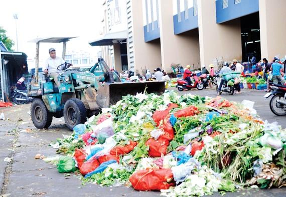 Thu dọn rác tại một bãi tập kết rác ở chợ Bình Điền                                                                                     Ảnh: THÀNH TRÍ