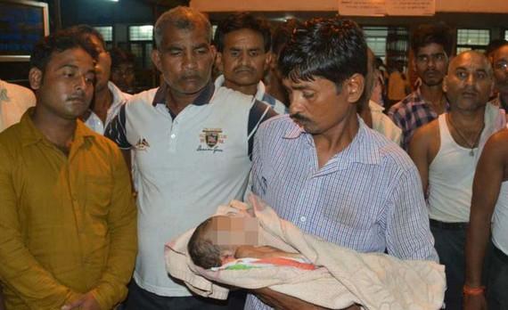 Một người đàn ông bế một trẻ nhi đã tử vong ở bên ngoài Bệnh viên Cao đẳng Y khoa Baba Raghav Das. Ảnh: AP