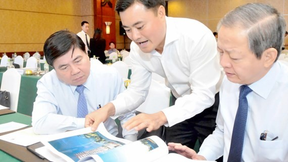 Chairman of the HCMC People's Committee Nguyen Thanh Phong (L) and deputy Le Van Khoa (R) see an construction work sketch at the conference on June 14 (Photo: SGGP)