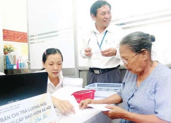 The old woman receives social insurance premium at an agency in HCMC (Photo: SGGP)