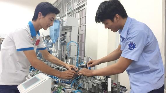 Hải (bên phải) và Tiến tập luyện để chuẩn bị cho kỳ thi tay nghề ASEAN  lần thứ XI