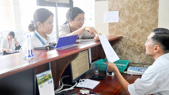 Doanh nghiệp nêu thắc mắc cần giải đáp với nhân viên Cục thuế TPHCM. Ảnh: THÀNH TRÍ