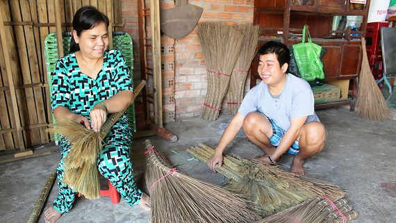 Chị Lam đang hướng dẫn cho một người đồng cảnh ngộ cách làm chổi