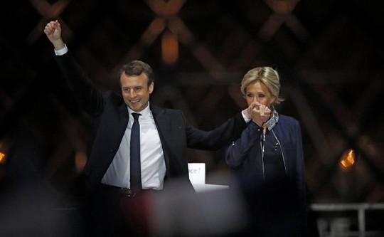 Ông Macron và vợ Brigitte Trogneux mừng chiến thắng tại Paris hôm 7-5. Ảnh: Reuters