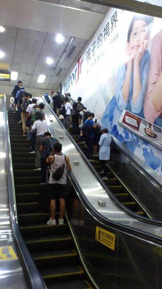 乘客在台北地鐵乘自動扶梯。
