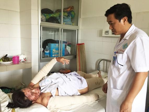 秦玉山醫生在問診灼傷者翁氏簪。(圖源:H.Hoa)