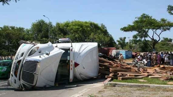 Hiện trường xe đầu kéo chở gỗ bị lật ngang khiến QL1A bị ách tắc. Ảnh: HUY ĐẠT