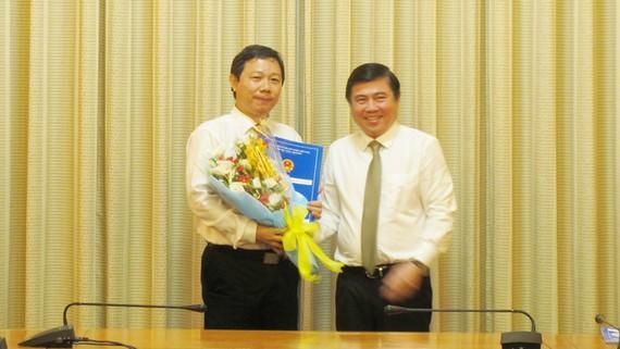 Chủ tịch UBND TPHCM Nguyễn Thành Phong (phải) trao quyết định và tặng hoa chúc mừng đồng chí Dương Anh Đức, Giám đốc Sở Thông tin và Truyền thông.