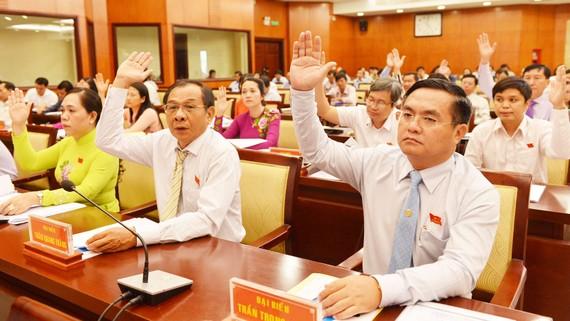 Các đại biểu HĐND TPHCM biểu quyết thông qua nghị quyết kỳ họp. Ảnh: VIỆT DŨNG