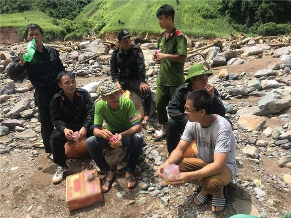 Soldiers and volunteers make a quick meal of instant noodles before continuing their work to carry food and other necessities to flood-hit residents in Yen Bai Province. — Photo thethaovanhoa.vn