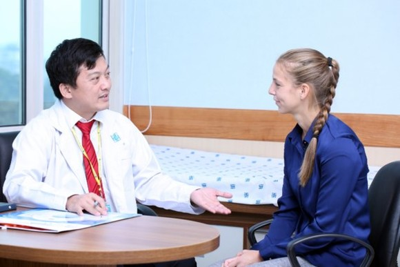 A doctor talks to a foreign woman about her symptoms (Photo: SGGP)