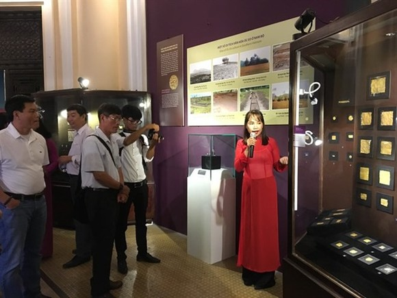 """Visitors listen to discussions about Oc Eo jewelry at the exhibition """"Bau vat Vuong quoc co - Nghe thuat kim hoan va trang suc Oc Eo"""" (Treasures of Ancient Kingdom – Oc Eo Jewelry and Ornament) at the HCM City Museum of History (Photo: VNA)"""