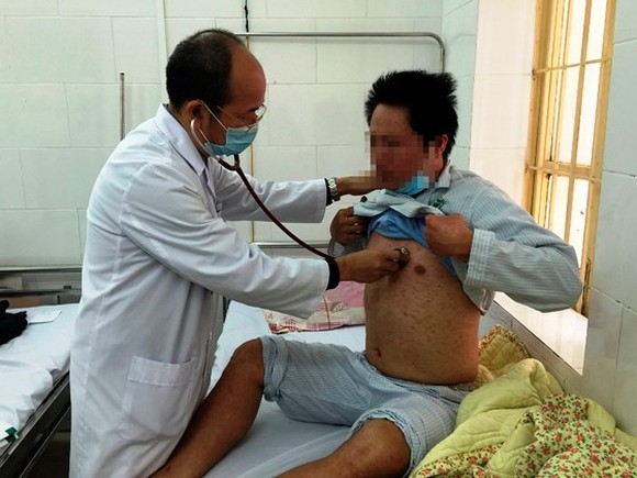 A medical worker is examining an adult suffering measles in Hanoi (Photo: SGGP)
