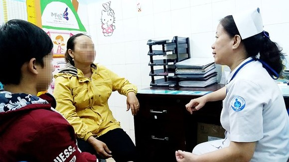 A medical worker is talking to a parent and her kid at the department (Photo: SGGP)