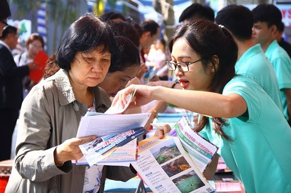 A visitor is finding out information of tours at the festival (Photo: SGGP)
