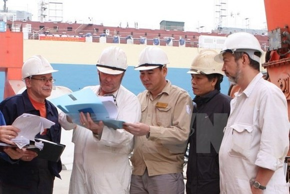 Foreign and Vietnamese workers at a construction site (Photo: VNA)