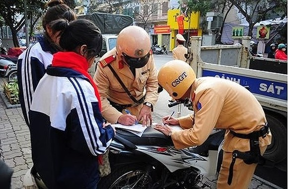 Police officers write ticket to fine two students who violate the traffic law (Photo: SGGP)