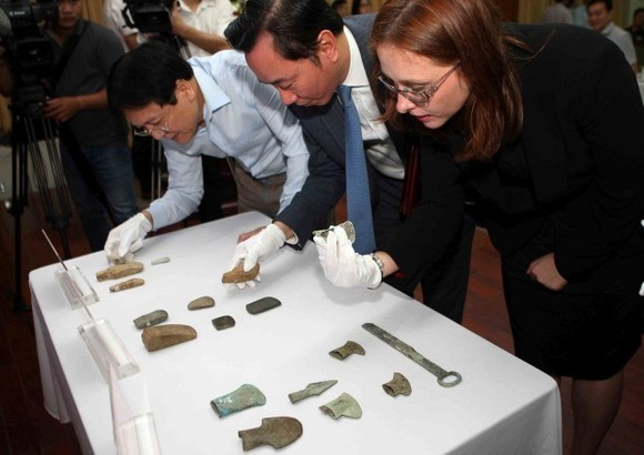 Officials examine the antiques at the hand-over ceremony (Photo: VNA)