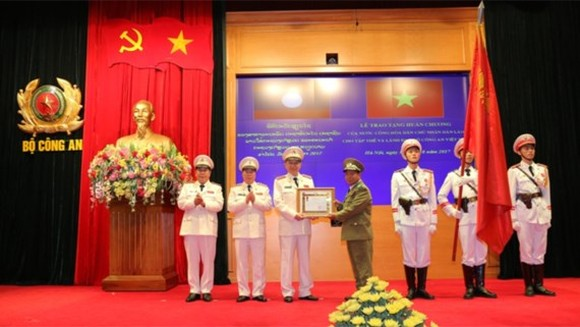 Lieutenant General, Minister of Security of Laos Somkeo Silavong  offers the first-class Development Medal of Lao People Democratic Republic to Ministry of Public Security of Vietnam