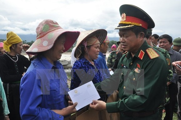 National Assembly Vice Chairman Do Ba Ty (R) visits flood victims in Yen Bai province on October 18 (Photo: VNA)