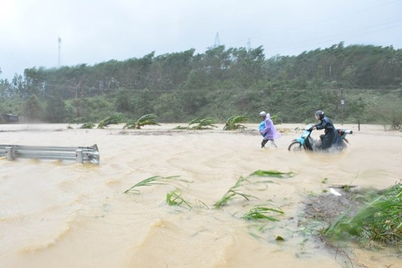 People wade through floodwater on Bridge 14, part of National Highway 26 in the Central Highlands province of Dak Lak, on November 4 morning, when storm Damrey hit the central coast (Photo: VNA)