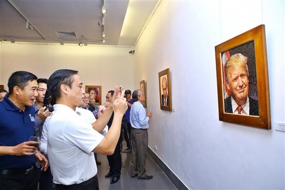 Visitors take a photo of a mosaic ceramic painting of US President Donald Trump (Photo: VNA)