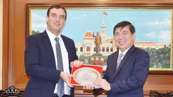 Chairman of the Ho Chi Minh City People's Committee Nguyen Thanh Phong offers a souvenir to Israel Ambassador to Vietnam Nadav Eshcar