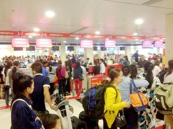 Passengers wait for their turns at airport check-in counters (Photo: SGGP)