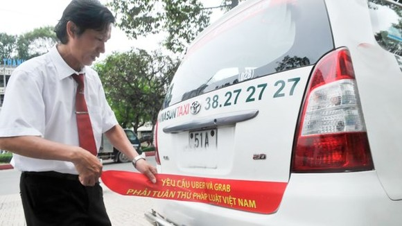 A driver removes the red banner protesting against Uber and Grab in HCMC street (Photo: SGGP)